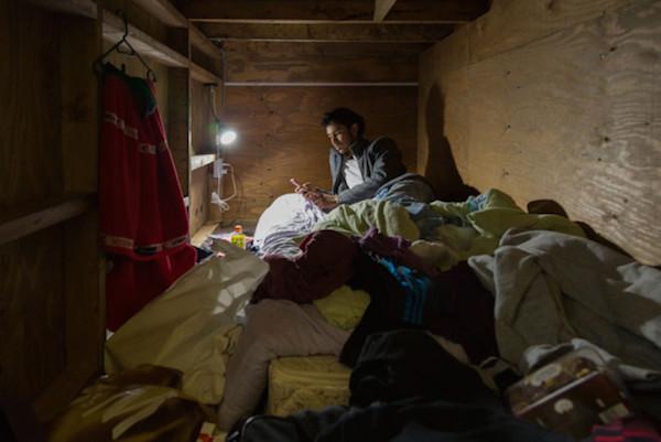 Un hombre recostado de lado en su estrecho cuarto que por un orificio entra el sol