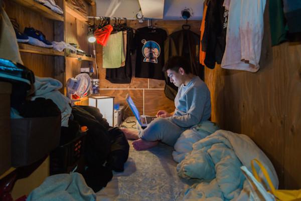 Un hombre navega en su computador en su estrecho cuarto