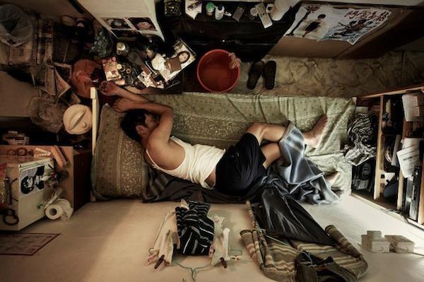 Un hombre duerme en su cuarto con sus pertenencias muy regadas