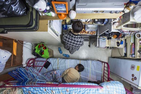 Un joven cocinando al lado de su cama, mientras su hijo duerme