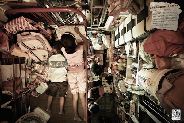 Dos niños en el ultimo nivel de una cama en un cuarto poco ancho pero muy largo