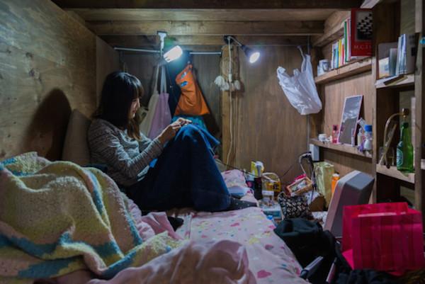 Una mujer viendo su celular sentada en la cama
