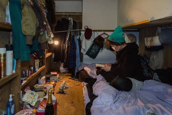Una mujer sentada con tapabocas en su cama
