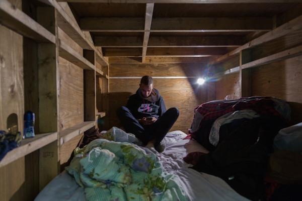 Hombre mirando su telefono en su dormitorio