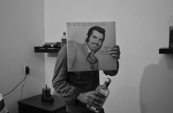 Vemos un hombre joven  sonriendo que siostiene su propio LP  en la mano llevandolo a su rostro sostiene un botella en su mano