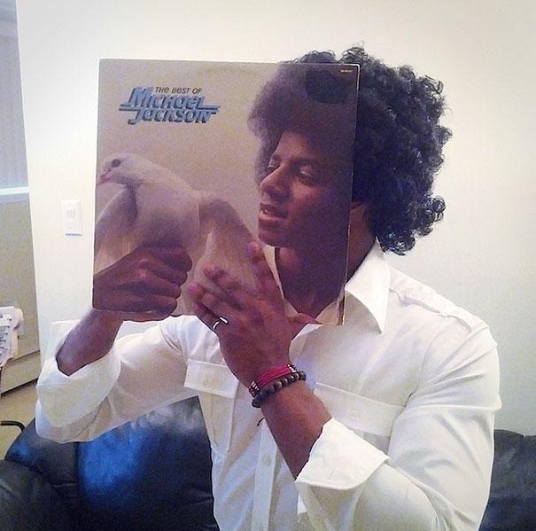 Vemos a un hombre joven con una caratula de un LP donde esta su rostro sostiene una paloma en sus manos lo sobre  su  rostro