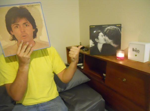 Vemos a Jhon lLennon con un vidrio que muestra su cara y se ve como si fuera la caratula de un disco tambien vemos una fotografía de Lenon y Yoko Ono