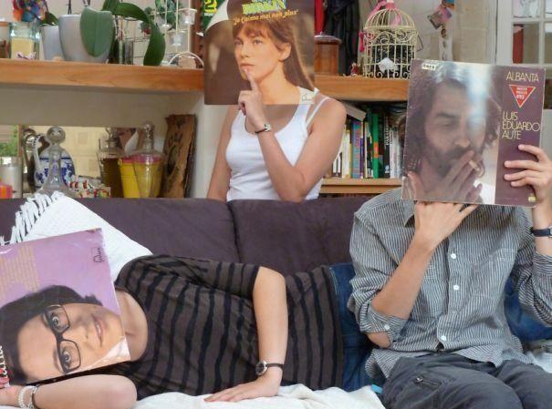 Observamos dos hombres y una mujer la mujer sentada atrás del sofá otro sentado y el otro acostado cada uno sostiene una caratula de LP en su rostro y lo iguala con su cuerpo