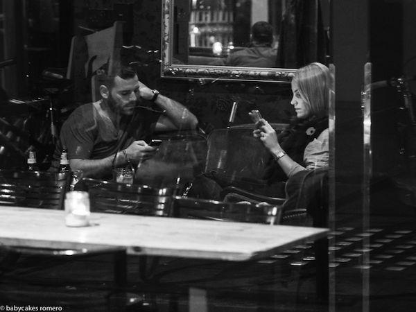vemos una pareja cada uno con celular en un sitio de café