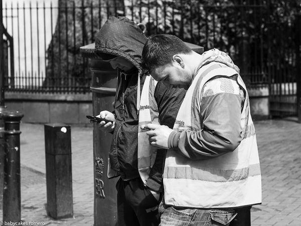 Vemos como dos hombres con chaquetas con capucha observan sus celulares en una calle