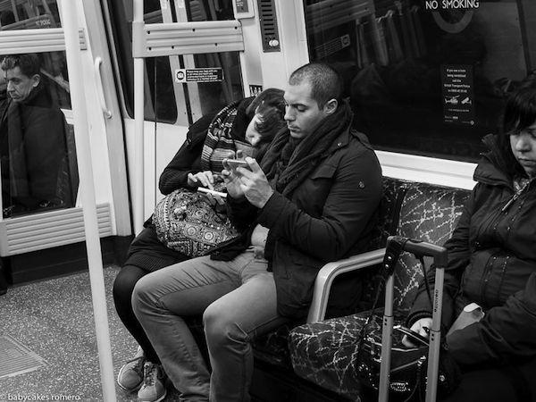 Veo a una pareja dentro del metro cada uno observa su celular  se ven mas personas allí  adentro