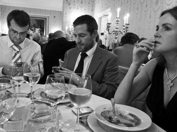 Tenemos en un elegante salón a varias personas disfrutando de una gran cena mientras todas observan sus celulares