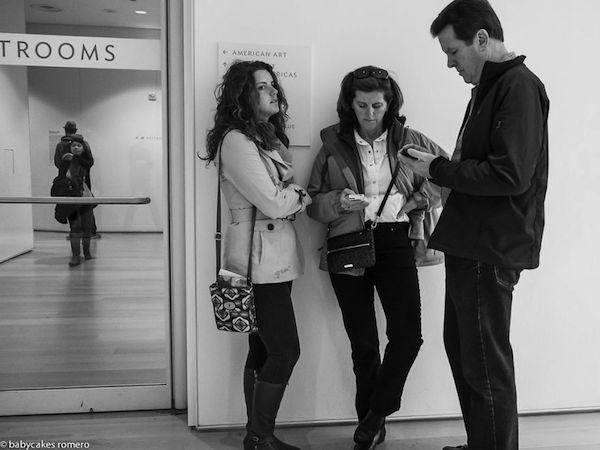 Vemos a tres personas dos mujeres y un hombre todos observan sus celulares están  al lado de una puerta