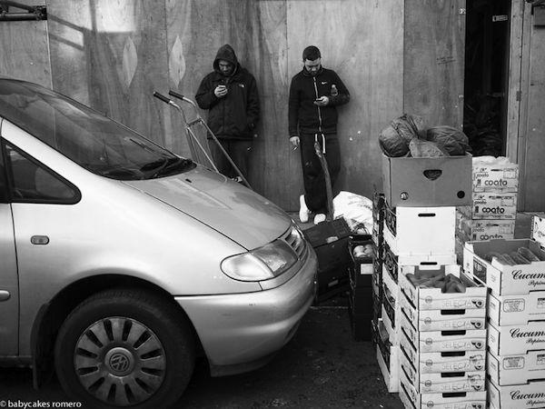 Observamos a dos hombres en la entrada a un deposito de verduras hablando con sus celulares