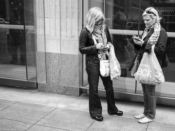 Tenemos a dos mujeres rubias con ropade frio que miran sus celulares despues de haber hecho la compra