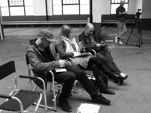 Vemos como tres personas dos hombres y una mujer al centro sentados miran sus celulares al fondo una cuarta persona un hombre frente a una camara tambien observa su celular