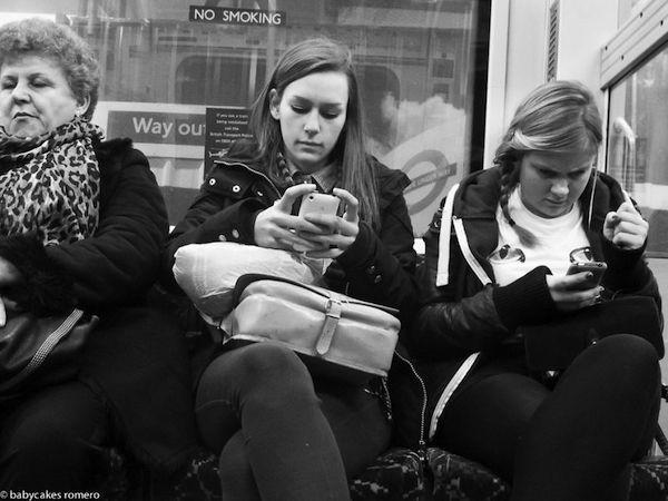 Tres mujeres sentadas dos jóvenes y una mayor miran sus celulares tranquilamente al fondo se observa una calle