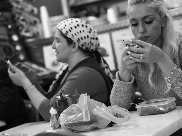 Vemos como dos mujeres comen  y las dos ven sus celulares una muy elegante la otra mas sencilla y con pañuelo atado a su cabeza