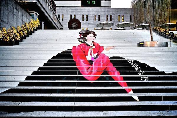 Escala en blanco y negro con una mujer sentada con un lindo traje en rosa fuerte al fondo se ve la hora y tambien unas sombrillas