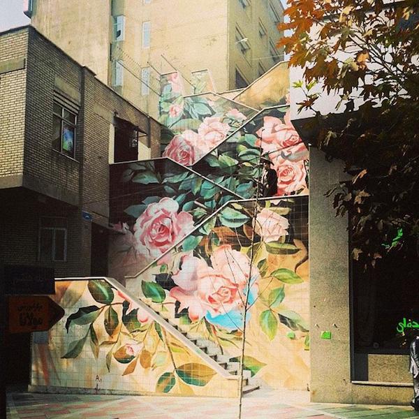 Vemos una  edificio con escala por fuera de el magnifica mente pintada con hermosas flores en colores  fuertes la escala llega pintada hasta el final