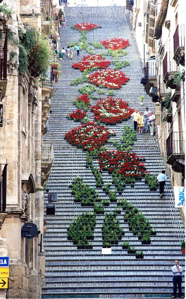 Que hermosa escala llena de flores y en azulejos dan un aspecto muy hermoso es ancha y espaciosa