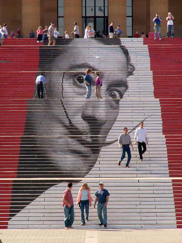Tenemos una escala en negro y rojo dode se pinto la imagen de Dali el pintor también vemos  personas que descansan en la misma escala