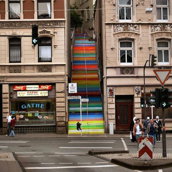 Vemos una escala en medio de dos edificios pintada en alegrs colores se ve tambien una calle  con varios carriles