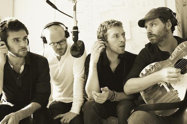 Cuatro músicos jóvenes uno toca guitarra los otros esperan