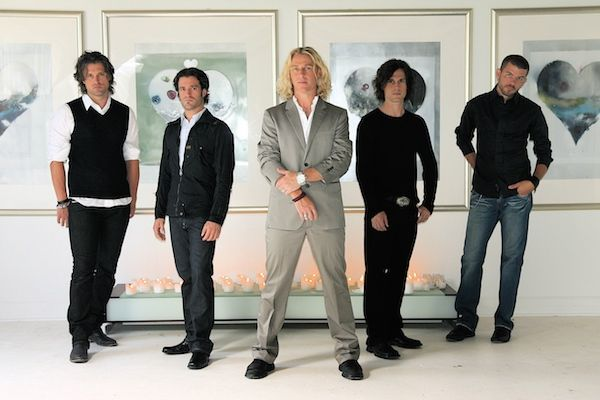 Cinco jóvenes cuatro de pelo oscuro y uno rubio con ropa clásica detrás de ellos se ven cuadros como de una galería
