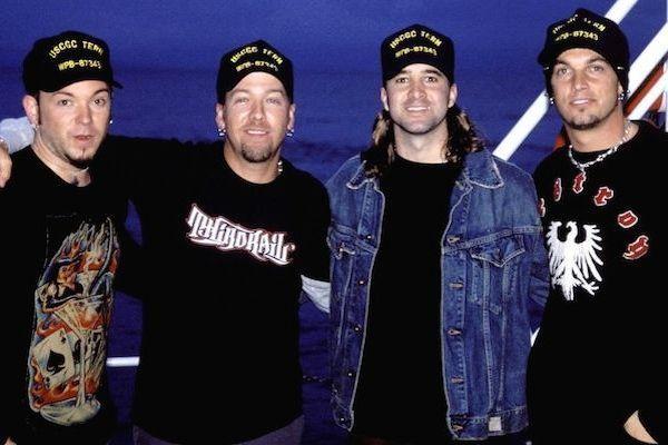 Cuatro jóvenes músicos todos con camisetas negras y gorras negras