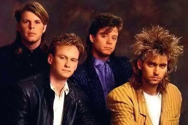 Un grupo de músicos muy jóvenes elegantes y miran sonriendo
