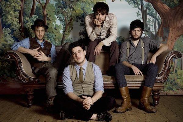 Cuatro músicos sentados en un sofá cada uno con trajes muy distintos