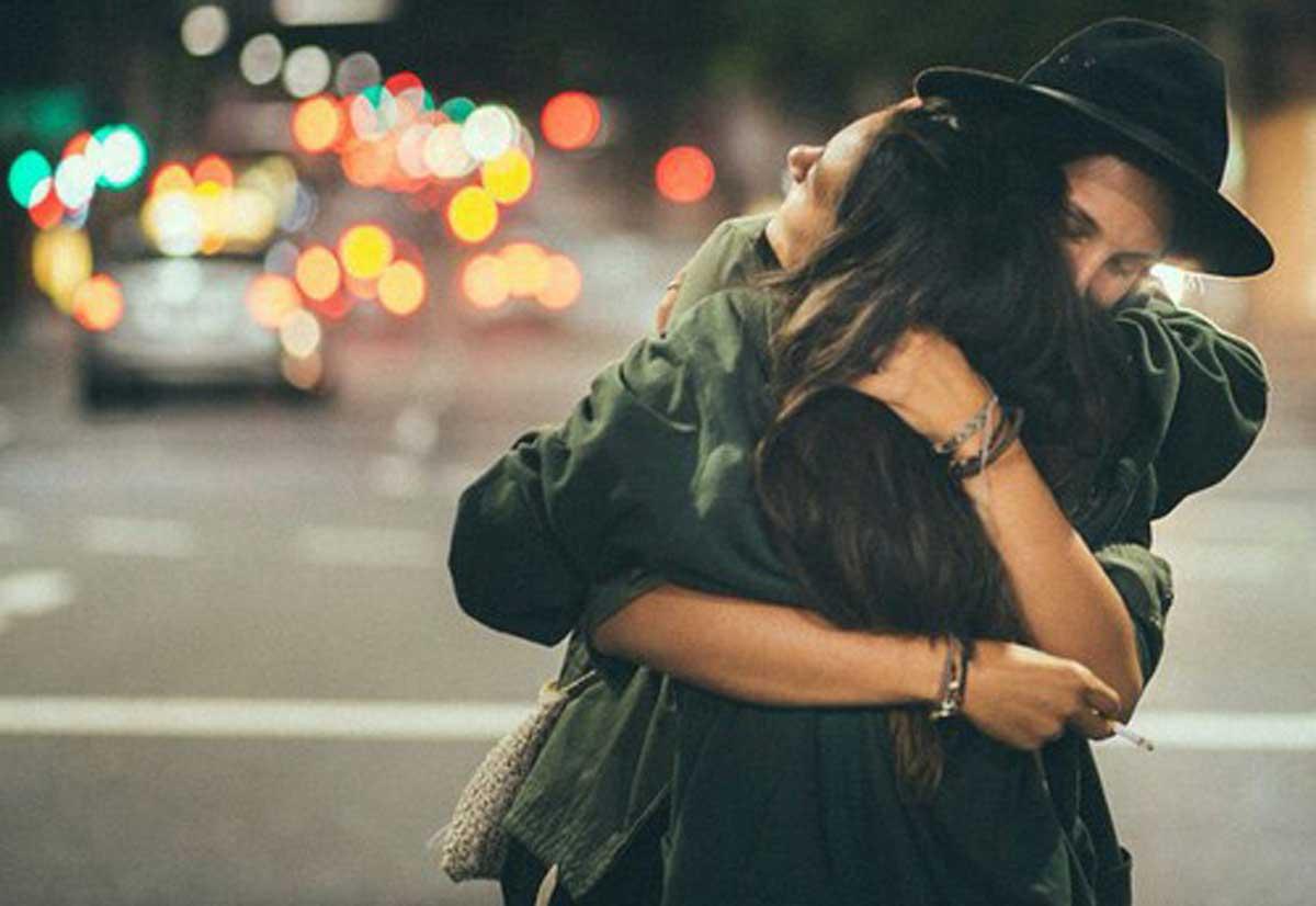 Vemos una pareja que se abraza con ternura el tiene un lindo sombrero