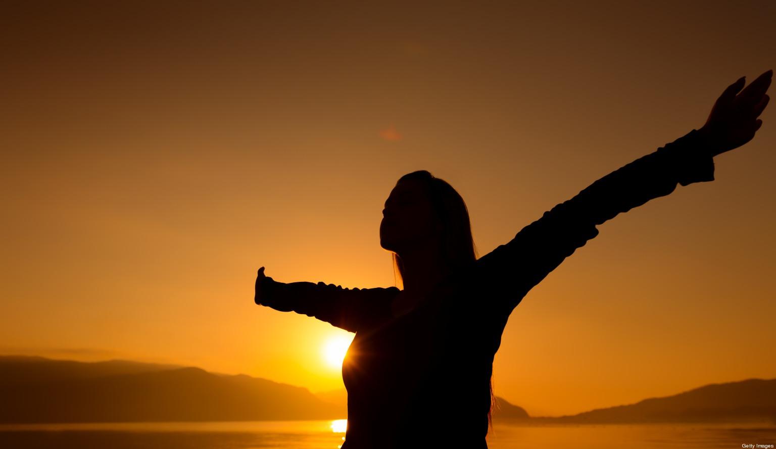 Vemos una mujer que en un lindo atardecer levanta sus brazos feliz