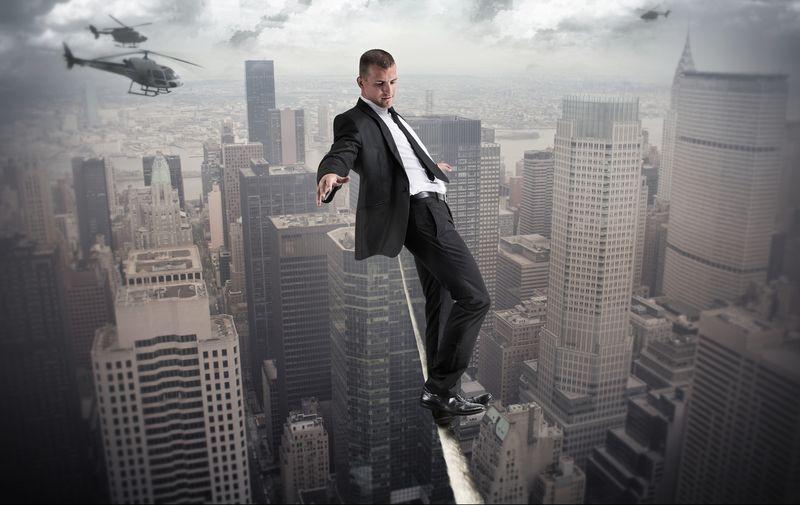 Vemos un hombre con traje y corbata que camina por una cornisa de un edificio muy alto y abajo edificios menos alto y vemos helicópteros volando