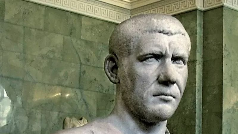 Un busto de un hombre joven con cabello muy corto con facciones fuertes