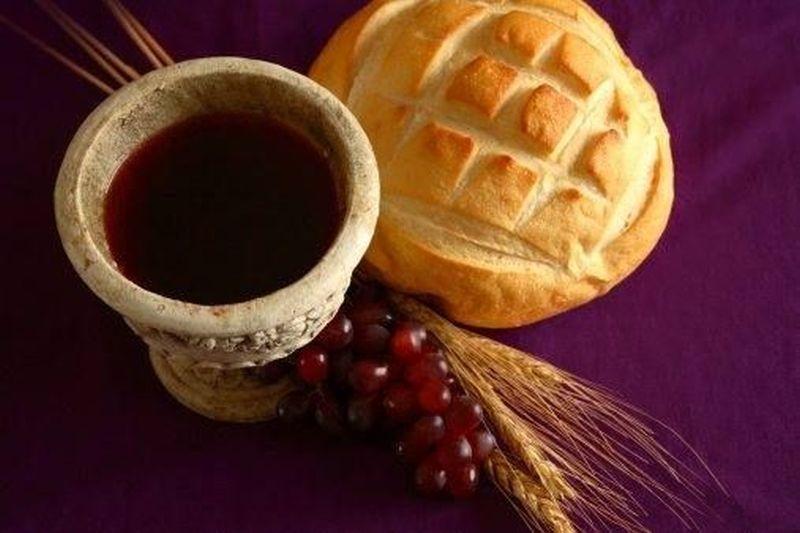 Un pan un recipiente con vino y unas espigas y un racimo de uvas