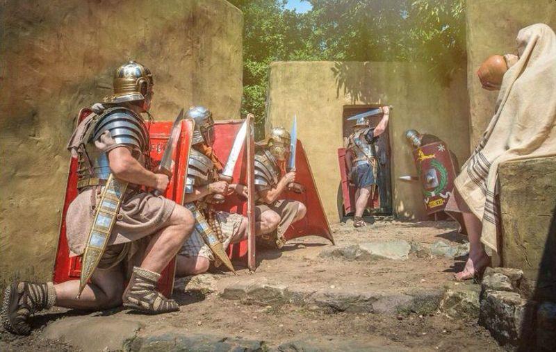 Unos hombres con cascos espadas y cascos y un hombre sentado con un chal