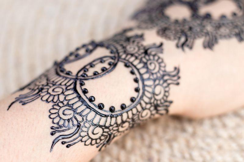 Un antebrazo donde hay pintado un tatuaje en forma de encaje