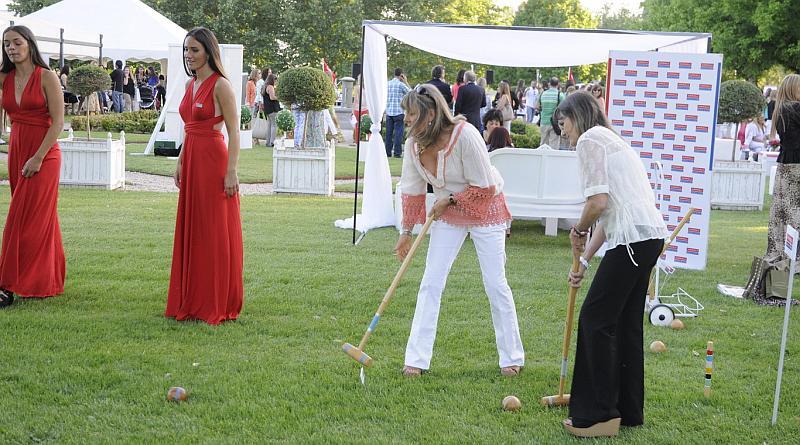 Vemos a dos mujeres tratando de introducir una pelota en un agujero y otras dos de vestido rojo miran la jugada