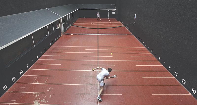 Tenemos iuna cancha de color rojo con lineas y números con una valla en la mitad  y los  jugadores a lados opuestos