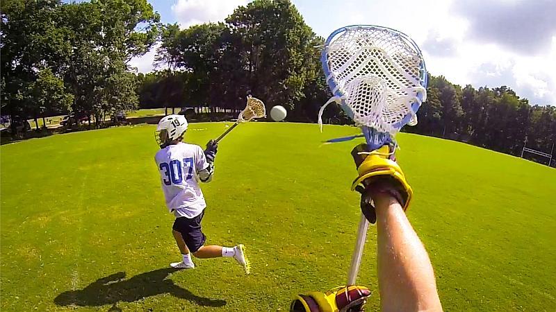 Vemos a dos jugadores con unos  palos con redes para atrapar una pelta ellos llevan cascos con protección