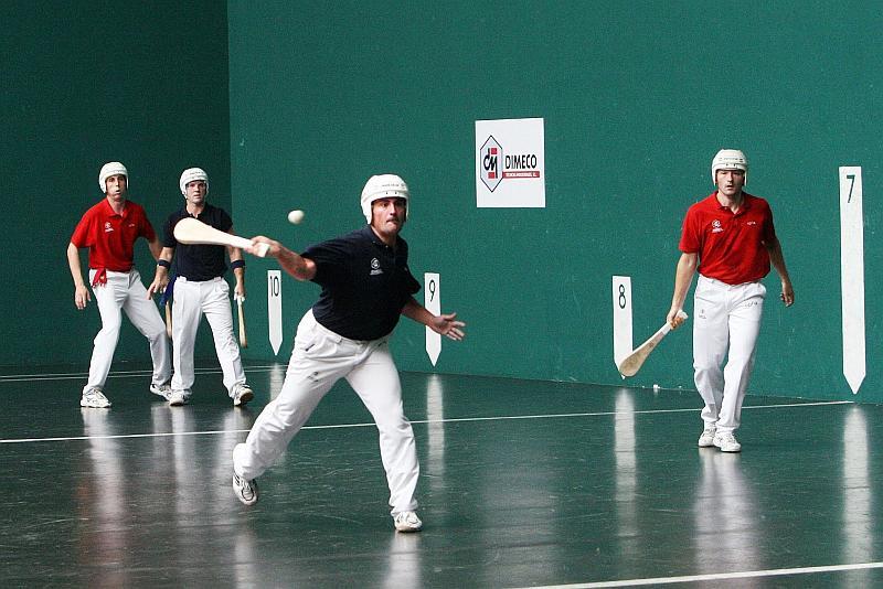Vemos a varios jugadores con uniforme y cascos sobre un piso tiene números y lineas y con una pequeña pelota que la impulsan  con paletas