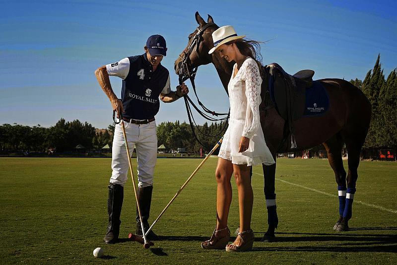 Vemos una  pareja y un caballo el leva uniforme y ella vestido tienen unos largos bastones y hay unas pelotas pequeñas en el piso