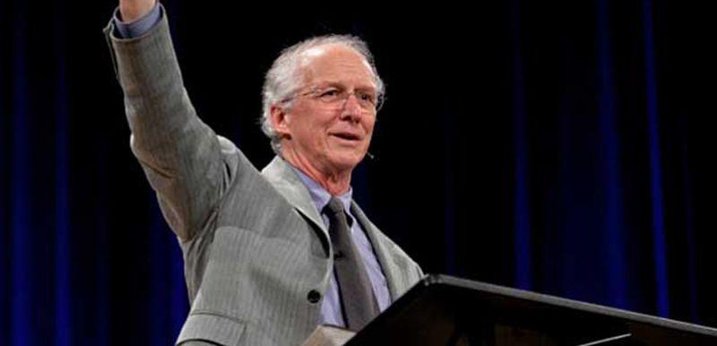 Hombre de avanzada edad, poco pelo y de traje mientras alza su mano en aparente predicación