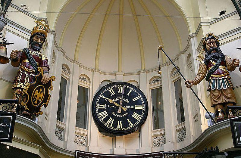 Foto a un reloj muy grande y dos esculturas a sus lados