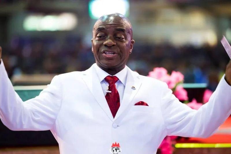 David Oyedepo con traje blanco, corbata roja y alzando sus dos brazos