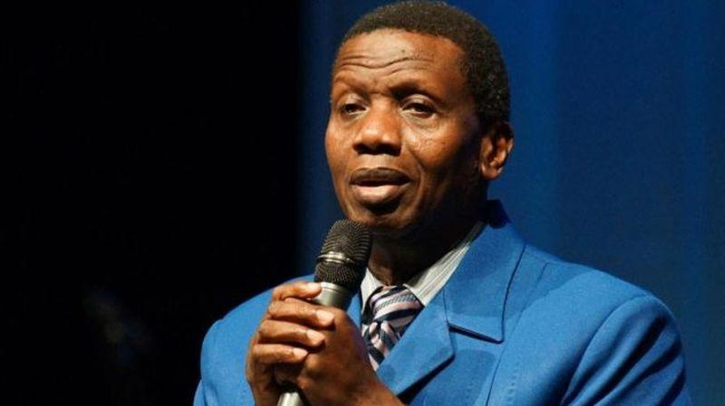 Enoch Adeboye con un traje zul sosteniendo un micrófono