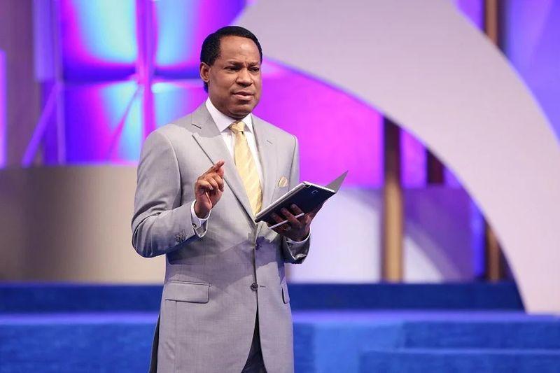 Chris Oyakhilome con traje gris y el la mano tecnologia de buena gama