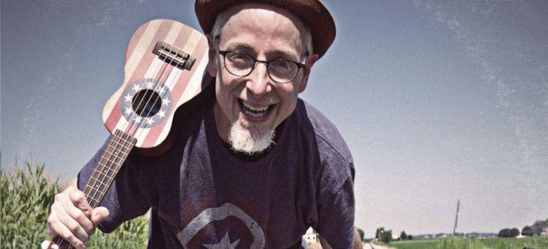 Una persona con un ukulele en su hombro el cual tiene el diseño de la bandera de Estados Unidos